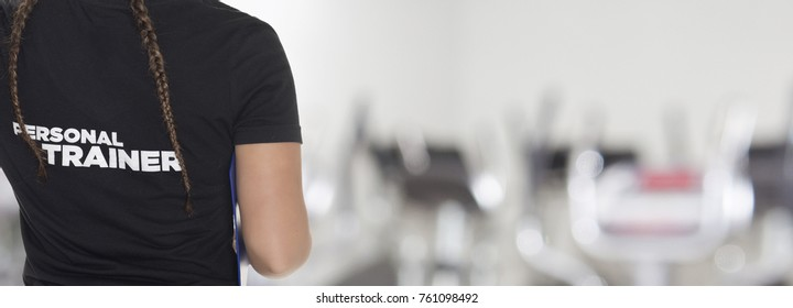 Female Personal Trainer, with his back facing the camera, looking at a gym