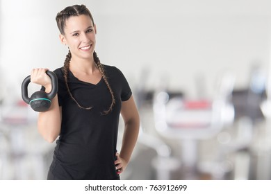 Female Personal Trainer, holding a kettlebell, in a gym