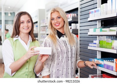 Female Pharmacist Advising Customer At Pharmacy In Front Of Shelves With Pharmaceuticals.