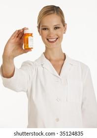 female pharmacist holding up bottle of pills