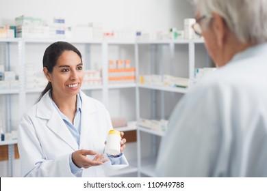 Female pharmacist holding a drug box in hospital