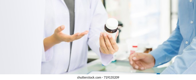Female pharmacist holding medicine bottle giving advice to customer in chemist shop or pharmacy - horizontal web banner with copy space on the left