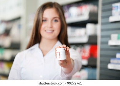 Female pharmacist looking at camera recommending medicine