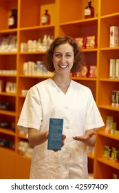 Female pharmacist pointing to medicine in her hand