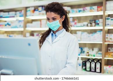 Apothekerin mit Schutzmaske auf ihrem Gesicht, die in der Apotheke arbeitet. Konzept der medizinischen Versorgung.