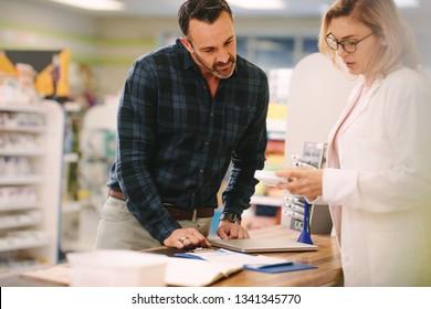 Female pharmacist showing medicine to male customer in pharmacy. Chemist suggesting medical drug to buyer in pharmacy drugstore.