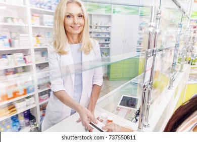 female pharmacist smiling at camera while taking credit card from customer in drugstore