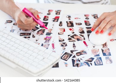 Female photo editor working on a contact sheet with a pink marker
