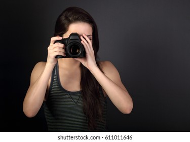 Female photograph in casual clothing holding camera and making the photo on dark background with empty copy space. Closeup portrait