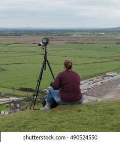 Female Photographer with a Camera on a Tripod on Top of Brean Down, a Limestone Promontory in the Bristol Channel and part of the Mendip Hills in Somerset, England, UK