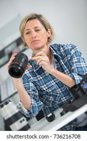 female photographer cleaning the camera lens