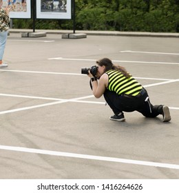 A female photographer with DSLR camera is secretly taking pictures of someone in exhibition outdoors. Moscow - June 1, 2019. Hidden photographing, paparazzi concept