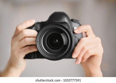 Female photographer holding camera on blurred background