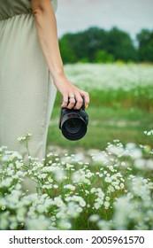Weibliche Fotografen, die eine Kamera im Freien auf der Blumenlandschaft halten, halten unerkennbare Frauen Digitalkamera in ihren Händen. Reisen Sie Naturfotografie, Platz für Text.