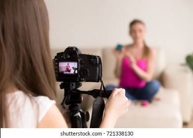 Female photographer looking at contemporary camera display, adjusting angle, preparing to take photo or video of girl sitting on sofa. Commercial product shoot, fashion photography, modeling concept.