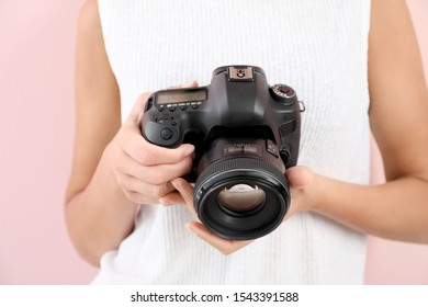 Female photographer on color background, closeup