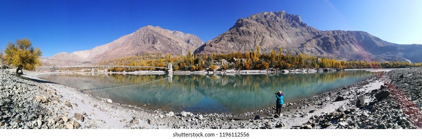 Female photographer with Panorama view of the Colorful autumn landscape with green crystal water of Indus river, Rock mountains, Blue sky and  in Khaplu valley of Skardu, Pakistan