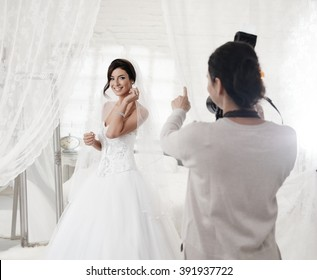 Female photographer photographing beautiful happy bride indoors.