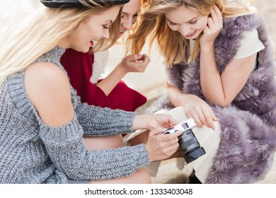 Female photographer showing fashion models results of photo shoot. Behind the scenes of professional modeling and photography industry.