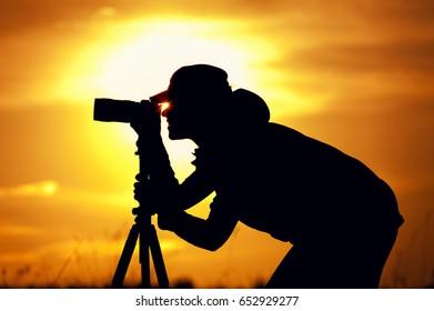 Female photographer silhouette at sunset light