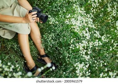 Weibliche Fotografen, die im Freien auf einer Blumenlandschaft sitzen und eine Kamera halten, halten unerkennbare Frauen Digitalkamera in ihren Händen. Reisen Sie Naturfotografie, Platz für Text, Draufsicht.