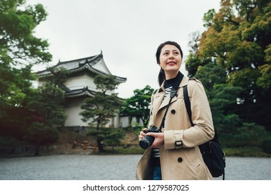female photographer standing outdoor sightseeing in japanese traditional old castle in kyoto japan. young cheerful girl traveler holding camera smiling looking up to sky visiting nijo jo in winter.
