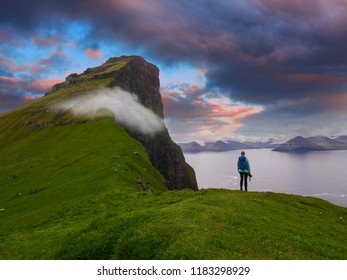 Female photographer stands on the edge of a cliff and watches the spectacular blue and orange evening sky. Stunning view of the magnificent green cliffs and mountains in the picturesque Faroe Islands.
