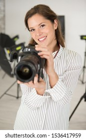 female photographer in the studio holding a camera