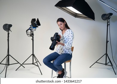 Female Photographer In Studio For Photo Shoot With Camera And Lighting Equipment