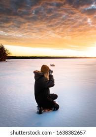 female photographer taking photo of animal on frozen lake during sunset