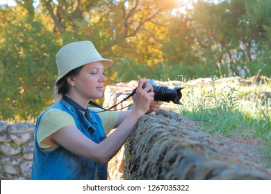 Female photographer taking photo in beautiful countryside. Photographer with camera outdoor. Summer time