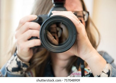 A female photographer taking a photo directly aimed at the viewer with a reflection in the lens.
