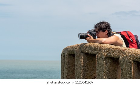 a female photographer taking a photograph, outdoors