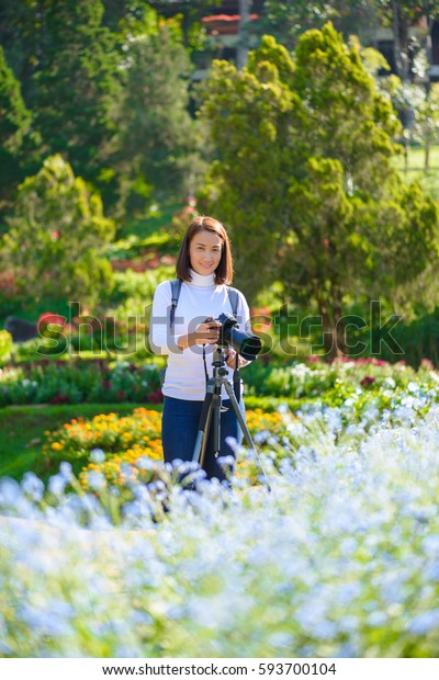 Female photographer with Tripod taking pictures of flowers in flowers garden