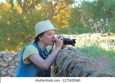 Female photographer working at countryside, shooting photographer outdoor. Summer time