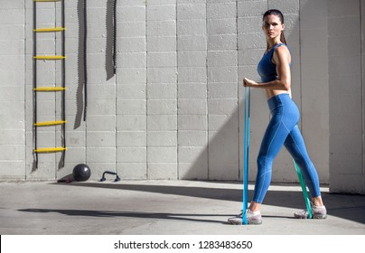 Female physical trainer holds strong posture with stretch bands, confident look, space