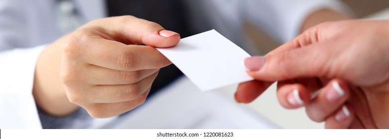 Female physician hand give white blank calling card to businesswoman closeup in office. Physical disease prevention examine patient instrument shop healthy lifestyle family doctor concept
