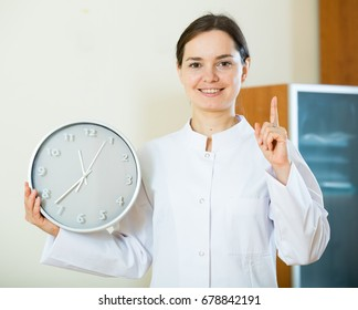 Female physician with stethoscope showing clock with schedule of work