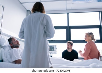 Female physician visiting patient in hospital room. Male patient lying in hospital bed with his friends and doctor.
