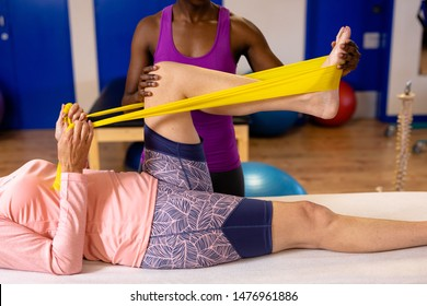 Female physiotherapist assisting woman to exercise with resistance band in sports center. Sports Rehab Centre with physiotherapists and patients working together towards healing