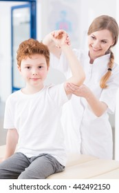 Female physiotherapist is checking the arm of young male patient