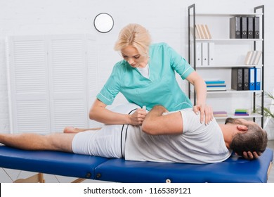 female physiotherapist doing massage to patient on massage table in hospital