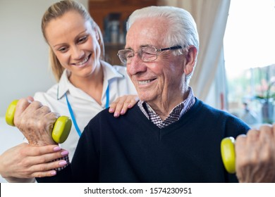 Female Physiotherapist Helping Senior Man To Lift Hand Weights At Home