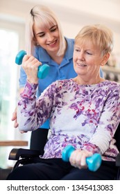 Female Physiotherapist Helping Senior Woman In Wheelchair To Lift Hand Weights