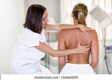 female physiotherapist inspecting her patient. Medical check at the shoulder in a physiotherapy center.