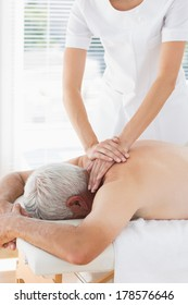 Female physiotherapist massaging back of senior patient in clinic