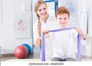 Female physiotherapist preparing her young patient to exercises