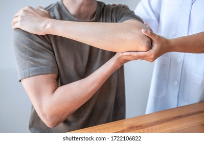 Female Physiotherapist working examining treating injured arm of athlete male patient, stretching and exercise, Doing the Rehabilitation therapy pain in clinic.