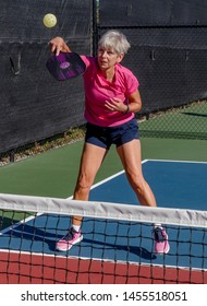 Female pickelball player volleys the ball over the net