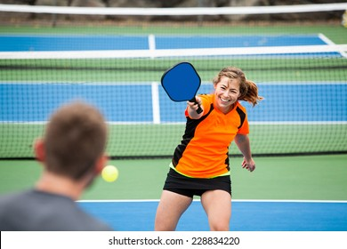 Female Pickleball player in action on an outside court